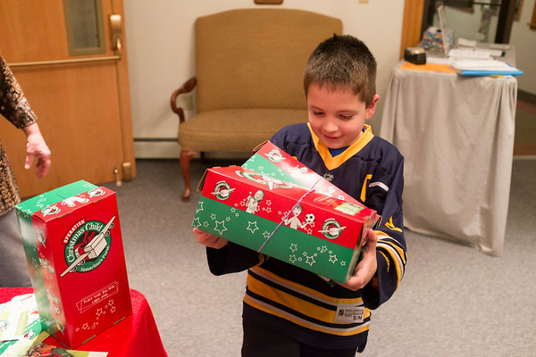 JOED VIERA/STAFF PHOTOGRAPHER-Cambria, NY- Keagan Schaal, 7,delivers two shoeboxes to Operation Christmas Child  at Community Bible Church.
