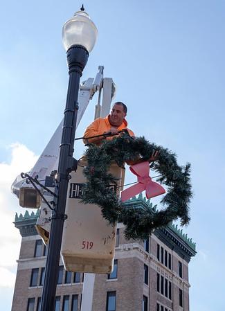 JOED VIERA/STAFF PHOTOGRAPHER-Lockport, NY- Randy Szymanski lifts a wreath up to a light fixture on Main Street.