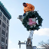 JOED VIERA/STAFF PHOTOGRAPHER-Lockport, NY- Randy Szymanski lifts a wreath up to a light fixture on Main Street.