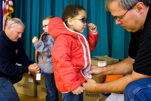 JOED VIERA/STAFF PHOTOGRAPHER-Lockport, NY-  Lockport City Firefighters Joe Prica and Kevin Seekins help Lucas Burke (grey) and Aaron Fuller(red) try on their new coats at Charles Upson.