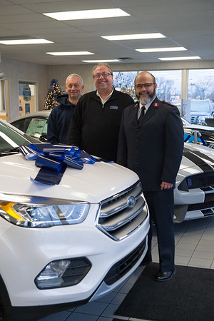 Joed Viera/ Staff Photographer- Lockport, NY-, Salvation Army Board Chairman Larry Eggert, Mike Landers and Salvation Army Major Jose Santiago at Howell Motors after Landers donated $2,000 to the organization.