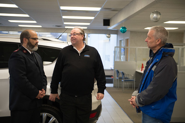 Joed Viera/ Staff Photographer- Lockport, NY-Salvation Army Major Jose Santiago, left, and chairman Larry Eggert, right, speak to Mike Landers at Howell Motors after Landers donated $2,000 to the organization.