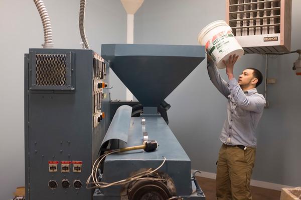Joed Viera/Staff Photographer Lockport, NY- Jake Balogh pours plastic shredding into Dan Dudek's plastic shaping machine at Next Level Plastics inside Harrison Place.