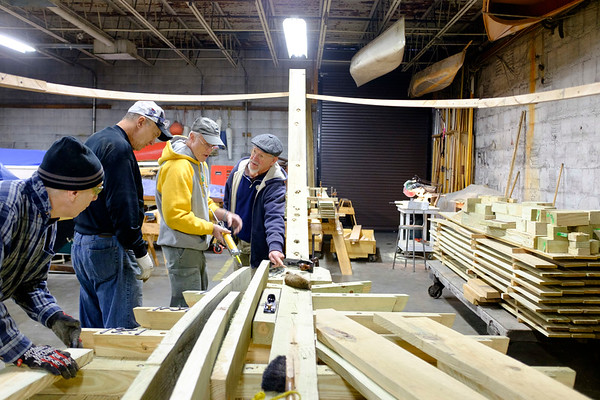 Joed Viera/Staff Photographer Buffalo, NY- Greg Garten, Jack Pittsley and Brian Braisted listen to Roger Allen as he explains where to put glue on the boat that will be used inside the flight of five at the Buffalo Maritime Center.