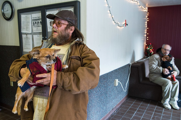 Joed Viera/Staff Photographer Lockport, NY-Tobin Little places a sweater on Freckles, his 1-year old long hair chihuahua as Rex Herl sits holding Weenie, his 10-year old, sweater-sporting Dachshund during Paulette Coty's visit to Urban Park Tower for Mario's Pet Food Pantry.