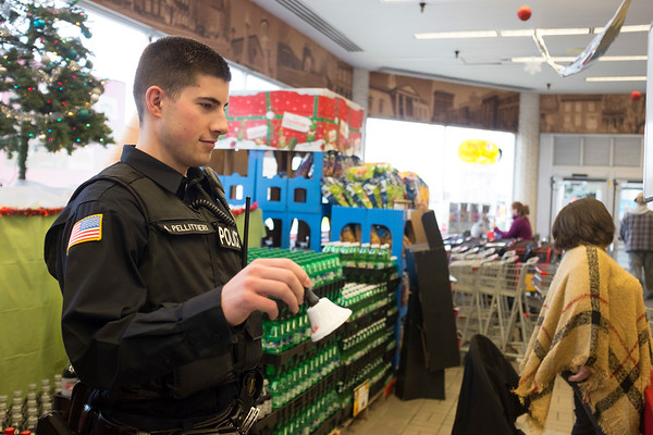 JOED VIERA/STAFF PHOTOGRAPHER-Lockport, NY-Lockport Police Department officer Anthony Pellittieri works a shift as a bell ringer for the Salvation Army's Kettle Drive at Tops.