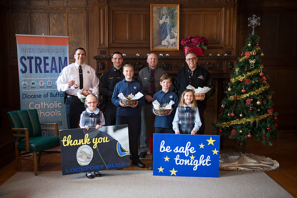 Joed Viera/Staff Photographer Lockport, NY- Niagara County Sheriffs Chief Deputy Steve Preisch, Deputy K. Hetrick, Trooper John Clarke and Zone Sergeant Sam Taglienti stand behind Samantha Fox, Eli Bohlman, Aaron Knuutila, and Courtney Parent at Desales Catholic School. Students at Desales gave the police departments craft ornaments to decorate their trees.