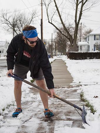 Joed Viera/Staff Photgrapher-Lockport, NY-Sporting shorts Josh Brennan casually shovels snow off of his Park Ave sidewalk.