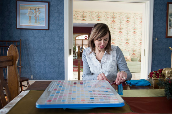 Joed Viera/Staff Photographer Lockport, NY-Donna Sholk and her husband have Scrabble parties to benefit the Buffalo Literacy center using a giant scrabble board. Scholk practices using the regular sized board game at her home on Friday.