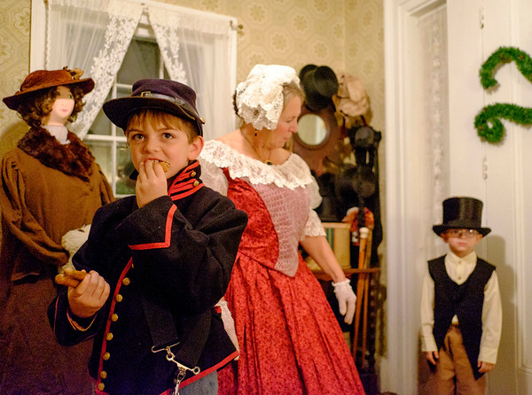JOED VIERA/STAFF PHOTOGRAPHER-Lockport, NY-  Connor Sherwood, 10, takes a break from drumming to enjoy a cookie as his grandmother Karen Sherwood and brother Max, 5, wait to greet guests at the Bond House on Thursday night.