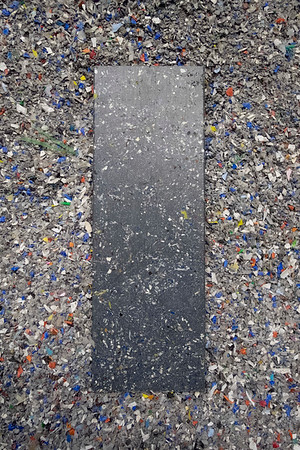 Joed Viera/Staff Photographer Lockport, NY- A board made from an assortment of recyclables sits atop shavings at Next Level Plastics inside Harrison Place.