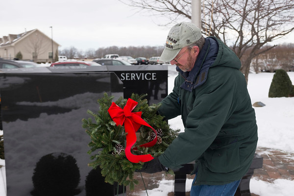 "Duty, courage, honor, valor and service are chiseled words between the names of the heroes engraved on the veterans memorial that stands outside of Niagara Hospice.  Members of the Vietnam Vets of America Niagara County's Gordon Bellinger places a holiday wreath on the memorial. Bellinger ended the annual ceremony by anchoring down the wreath next to the monument after delivering a short prayer ""To our past veterans with this holiday wreath may it say to those who have served our country before and with us: thank you, bless you and rest in peace"""