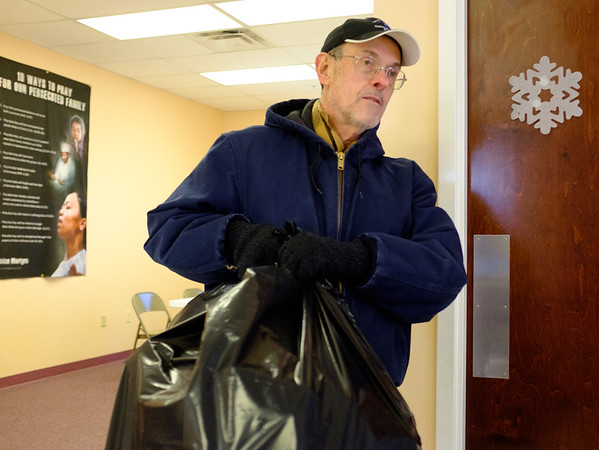 Joed Viera/Staff Photographer Newfane, NY-Gene Wood carries package to a client of the Salvation Army's Christmas Assistance Program.