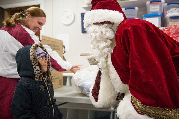 Joed Viera/Staff Photographer Lockport, NY- Sue Capell watches as Xaymarie Serrano, 5, meets Santa Clauss at the Youth Mentoring Service of Niagara County.