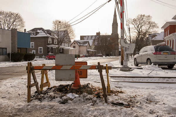 The remains of the railroad crossing pole lies on the snow at the intersection of Church and Green Streets. The pole was hit by a driver arrested on intoxication related charges.