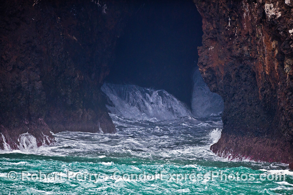 Image 2 of 3:  large swells roll up and crash inside the world-famous Painted Cave on Santa Cruz Island.