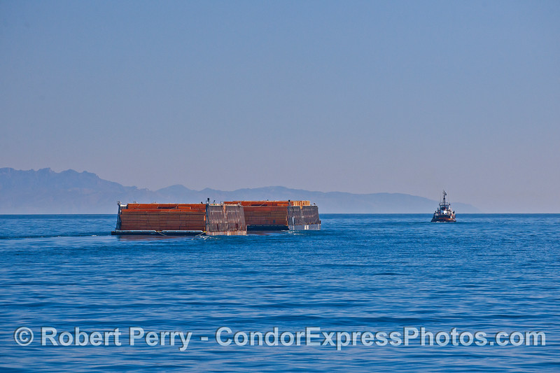 Two barge loads of lumber are seen being towed in the southbound shipping lanes of the Santa Barbara Channel.