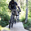Mountain bikers make their way across a wooden bridge on the trail Loosey Goosey, at Tabor Mountain on Saturday for the opening day of the bike park. Citizen Photo by James Doyle      July 16, 2016