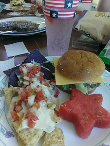 The whole meal - burgers, white and blue tortilla chips with white queso and pico de gallo, and star shaped watermelon.