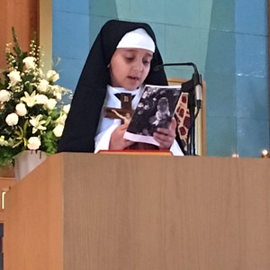 Naomi Ford (1st grade) as St. Theresa of Avila at the microphone      4:00PM Vigil Mass