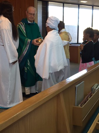 """Msgr. Gauthreaux accepting the gifts fromCCD """"saints"""""""