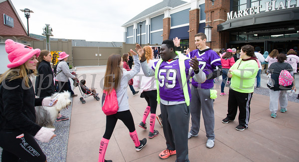 Members of the Monroe Woodbury Crusaders football team high-five people, including cancer survivors, their families and businesses, as they participated in the annual American Cancer Society Making Strides Against Breast Cancer walk at Woodbury Common Premium Outlets in Central Valley, NY on Sunday, October 16, 2016. Hudson Valley Press/CHUCK STEWART, JR.