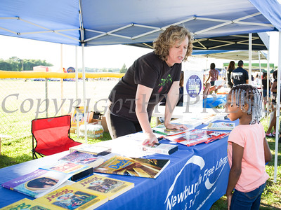 Newburgh Free Library Assistant Librarian Elizabeth Connelly hands out book during the 19th year of the all-free National Night Out event in the City of Newburgh on Tuesday, August 2, 2016. Hudson Valley Press/CHUCK STEWART, JR.
