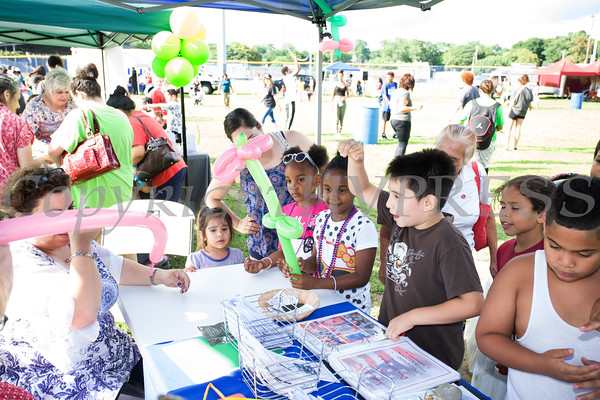 Olga Brandenberger of RECAP creates balloons for kids during the 19th year of the all-free National Night Out event in the City of Newburgh on Tuesday, August 2, 2016. Hudson Valley Press/CHUCK STEWART, JR.