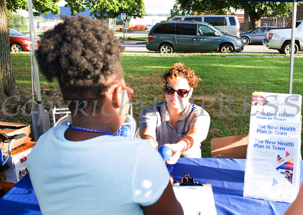 Jessica Betancourt hands out information about Crystal Run Health Plans during the 19th year of the all-free National Night Out event in the City of Newburgh on Tuesday, August 2, 2016. Hudson Valley Press/CHUCK STEWART, JR.