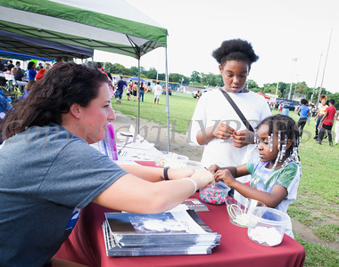 Lauren Savino of Alcoholism & Drug Abuse Council of Orange County creates a bracelet with La'Shyne Lewis and Jaylin Bechwith during the 19th year of the all-free National Night Out event in the City of Newburgh on Tuesday, August 2, 2016. Hudson Valley Press/CHUCK STEWART, JR.