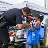 "Kids received a ""badge"" from P.O. Vasta during the 19th year of the all-free National Night Out event in the City of Newburgh on Tuesday, August 2, 2016. Hudson Valley Press/CHUCK STEWART, JR."