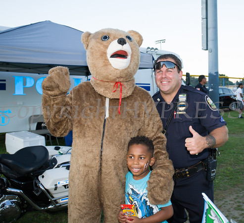 Children pose with the RECAP Bear and PO Vasta during the 19th year of the all-free National Night Out event in the City of Newburgh on Tuesday, August 2, 2016. Hudson Valley Press/CHUCK STEWART, JR.