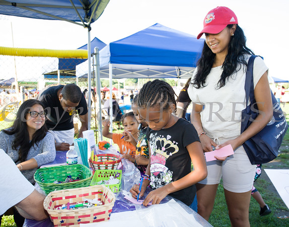 Laura Garcia assists at the Latinos Unidos of the Hudson Valley table during the 19th year of the all-free National Night Out event in the City of Newburgh on Tuesday, August 2, 2016. Hudson Valley Press/CHUCK STEWART, JR.
