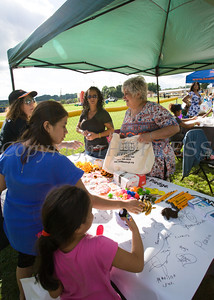 Diana King and Regina Cieslak of TEAM Newburgh hand out an assortment of goodies during the 19th year of the all-free National Night Out event in the City of Newburgh on Tuesday, August 2, 2016. Hudson Valley Press/CHUCK STEWART, JR.