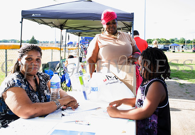 Kathleen Dawkins of Hudson Valley Community Services helps seven-year-old Glendon paint a picture during the 19th year of the all-free National Night Out event in the City of Newburgh on Tuesday, August 2, 2016. Hudson Valley Press/CHUCK STEWART, JR.