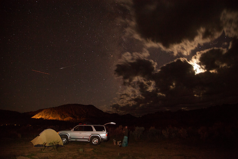 Tracy works over dinner while the moon goes behind a cloud over our camp in the Utah desert.