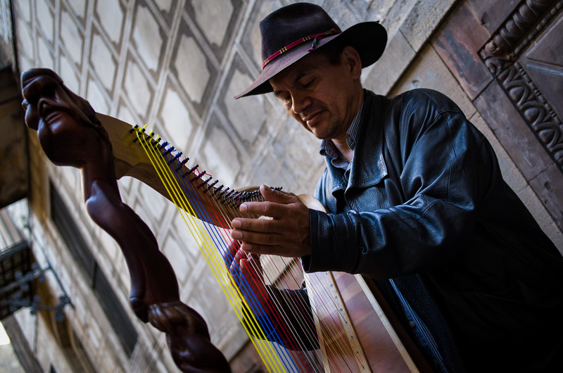 A harpist performs in the tight confines of Barri Gòtic. Barcelona, Spain.