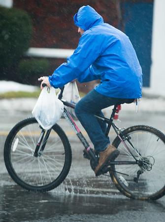 JOED VIERA/STAFF PHOTOGRAPHER- Lockport, NY-A man rides his bicyle through the rain on Washburn Street.