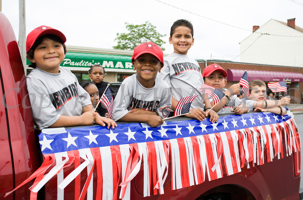 Children wave flags from the New Windsor Pediatrics float during the City of Newburgh hosted Memorial Day Parade on Monday, May 30, 2016, which proceeded along Broadway to Washington's Headquarters. Hudson Valley Press/CHUCK STEWART, JR.
