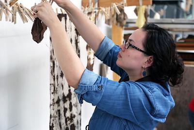 Maria Wood (MFA, Design Studies) hangs dyed fabric pieces.