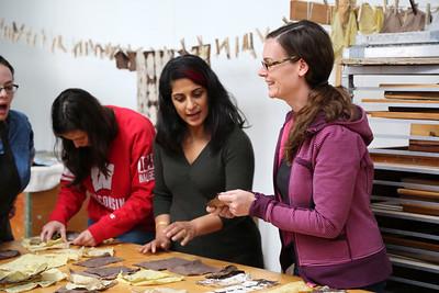 Left to Right: Maria Wood (MFA, Design Studies), Catherine Finedore (COE, Biomedical Engineering), Sarah K Khan, and Sarah O'Farrell (MFA, Art) examining fabric pieces.
