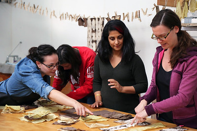 Left to Right: Maria Wood (MFA, Design Studies), Catherine Finedore (COE, Biomedical Engineering), Sarah K Khan, and Sarah O'Farrell (MFA, Art) look over dyed fabric.