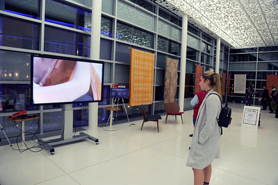 "An attendee watches sari draping on screen at the exhibition ""Tactile Textiles: Color and Culture"""