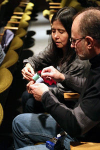 Audience members participating in a hands-on bioinspired art activity which illustrates how bees use circles to create hexagons for their honeycomb.