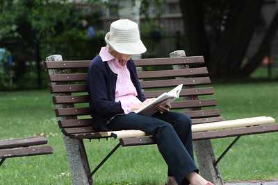 Woman reading on a bench, along the pathway
