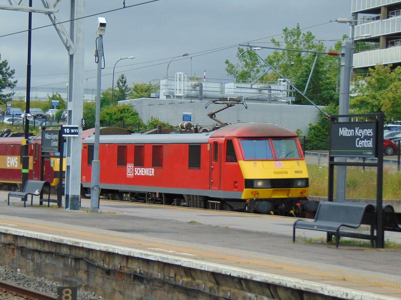 DB Cargo Class 90 no. 90029 hauling classmate 90035 through Milton Keynes Central.