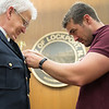 JOED VIERA/STAFF PHOTOGRAPHER- Lockport, NY-Lockport Police Chaplin Steven Antin's son and police officer Luke Antin places his badge during a ceremony at City Hall.