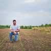 JOED VIERA/STAFF PHOTOGRAPHER- Lockport, NY-Jeff Hiller kneels on a patch of corn sprouts at Hiller's Farm.