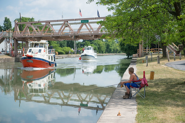 JOED VIERA/STAFF PHOTOGRAPHER-Middleport, NY- Gabriel Soulvie 13 watches a boat pass by while fishing in the Erie Canal Derby.