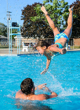 JOED VIERA/STAFF PHOTOGRAPHER- Lockport, NY-Matt Dussault launches his daughter Brionna, 9, into the air at the Lockport Community Pool.